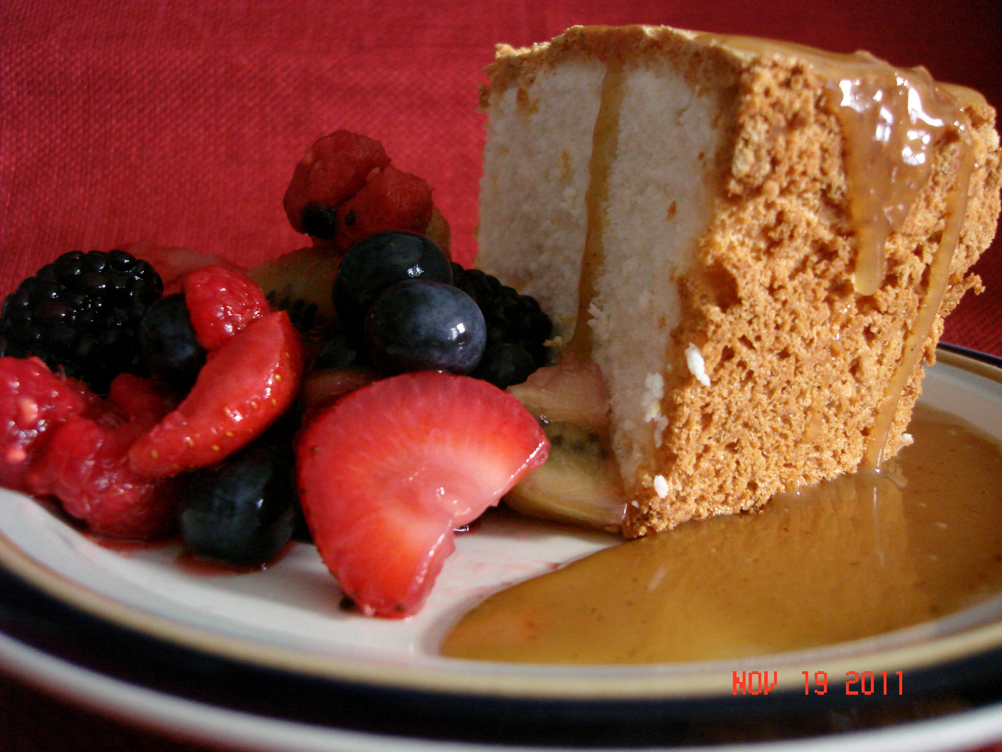 orange angel food cake with caramel sauce and four berry ...