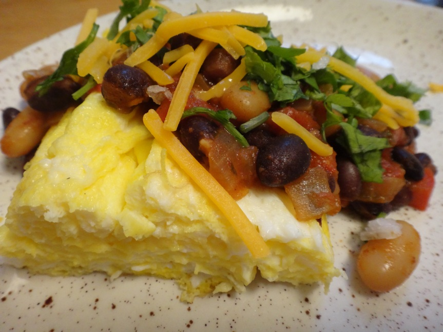 omelet with black and white bean chili, cheddar cheese, and chopped cilantro