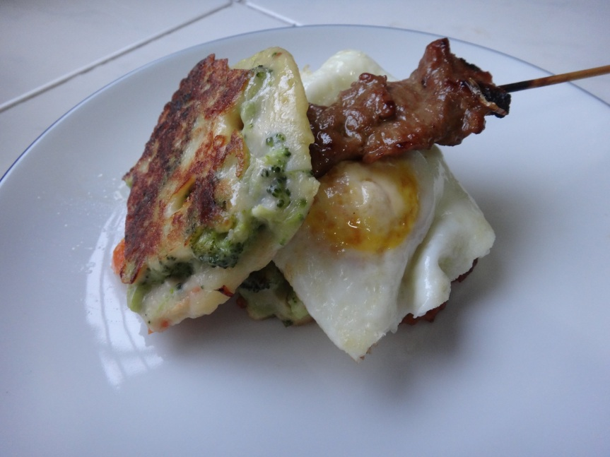 fried egg and gai yang (grilled pork) sandwiched between two broccoli-tomato fritters